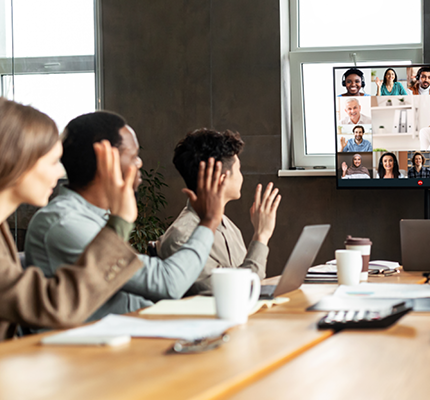 People raising hands looking at computer with conference meeting on screen