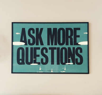 """Poster on wall that says """"Ask more questions"""""""