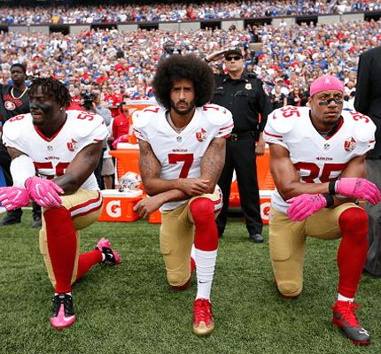 Three football players kneeling on one knee
