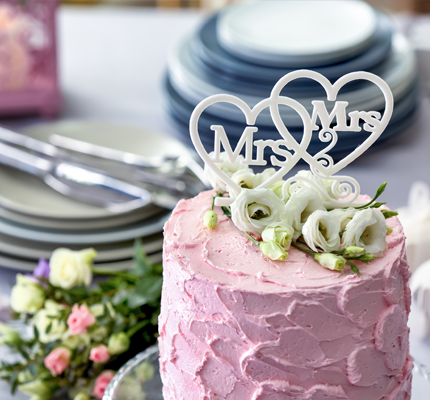 A pink wedding cake with Mrs. and Mrs. on the top.