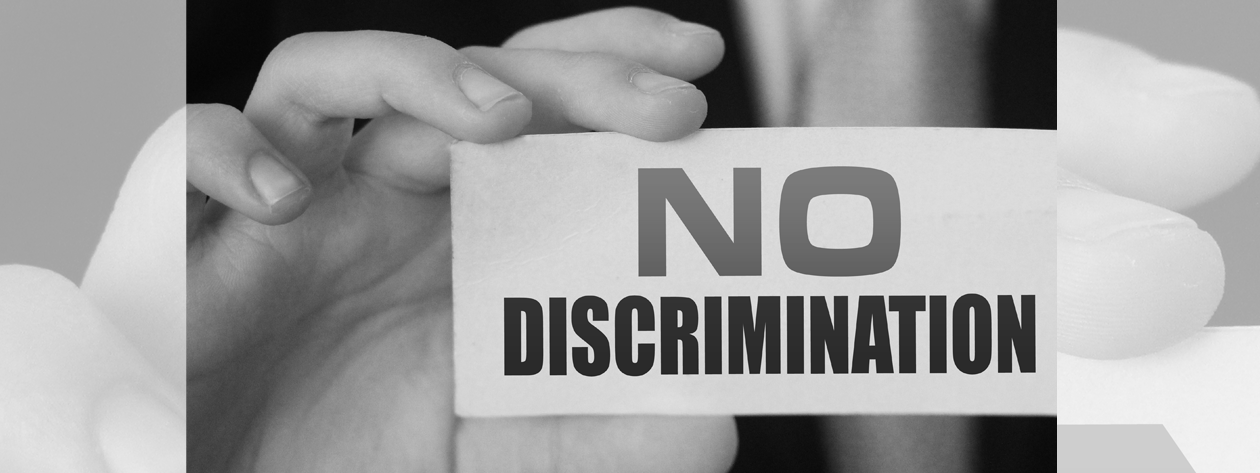 Hand holding card that reads No Discrimination